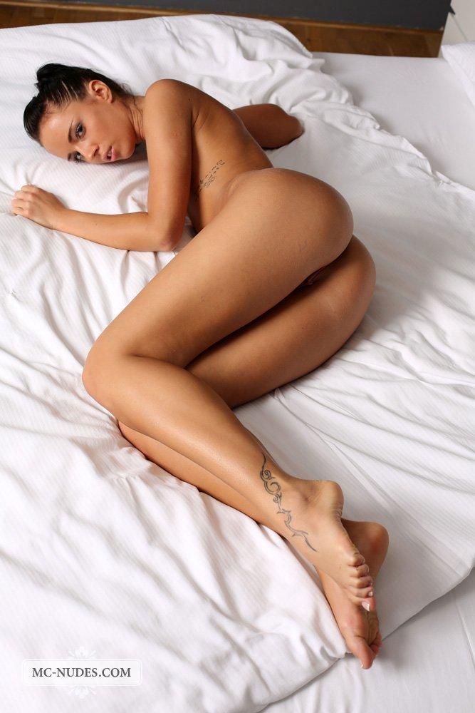 Симпатичная и подтянутая темненькая девушка Gina Devine обнажена на постели, обнажает свою пизду
